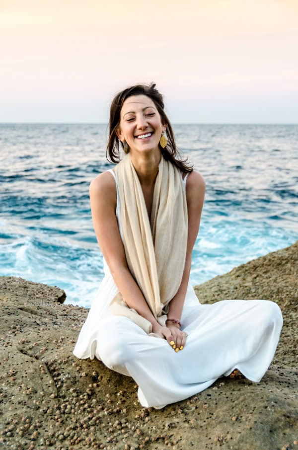 Jess osie sitting on a rock with the ocean behind her while smiling
