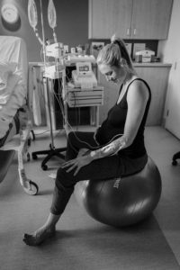 Navaya sits on gym ball in hospital with her hand on her pregnant tummy.