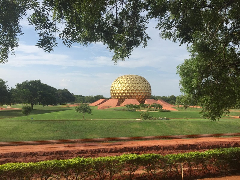 The Matramandir in Auroville, which looks like a golden sphere made of many circular golden tiles, sitting on a red soil based within green manicured lawns
