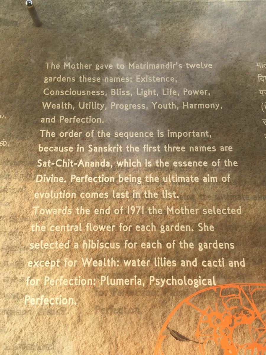 Plaque at The gardens of the Matramandir, which says 'The Mother gave to Matrimandir's twelve gardens these names; Existence, Consciousness, Bliss, Light, Life, Power, Wealth, Utility, Progress, Youth, Harmony, and Perfection. The order of the sequence is important, because in Sanskrit the first three names are Sat-Chit-Ananda, which is the essence of the Devine. Perfection being the ultimate aim of evolution comes last in the list. Towards the end of 1971 the Mother selected the central flower for each garden. She selected a hibiscus for each of the gardens except for Wealth: water lilies and cacti and for Perfection: Plumeria, Psychological Perfection.'