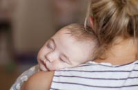 Baby's head resting comfortably on their mother's shoulder | Copyright Bright Photography