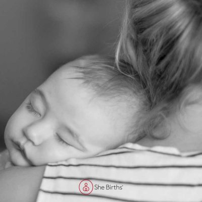 Baby being cuddled, showing baby head on mother's shoulder. Photo by Bright Photography