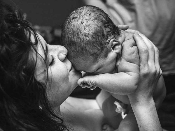 Photo of mother holding her new born child. Photo by Monet Nichole Photography.